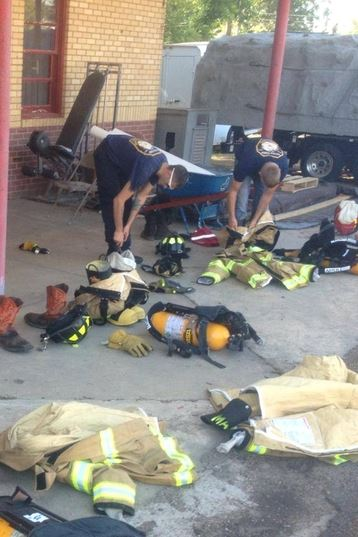 Two firefighters putting on their gear.